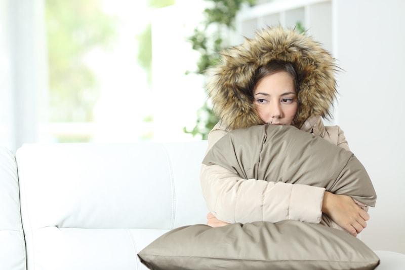 Angry woman warmly clothed in a cold home sitting on a couch