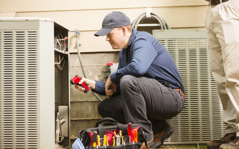 An HVAC technician in Grayslake, IL, servicing a homeowner's air conditioner.