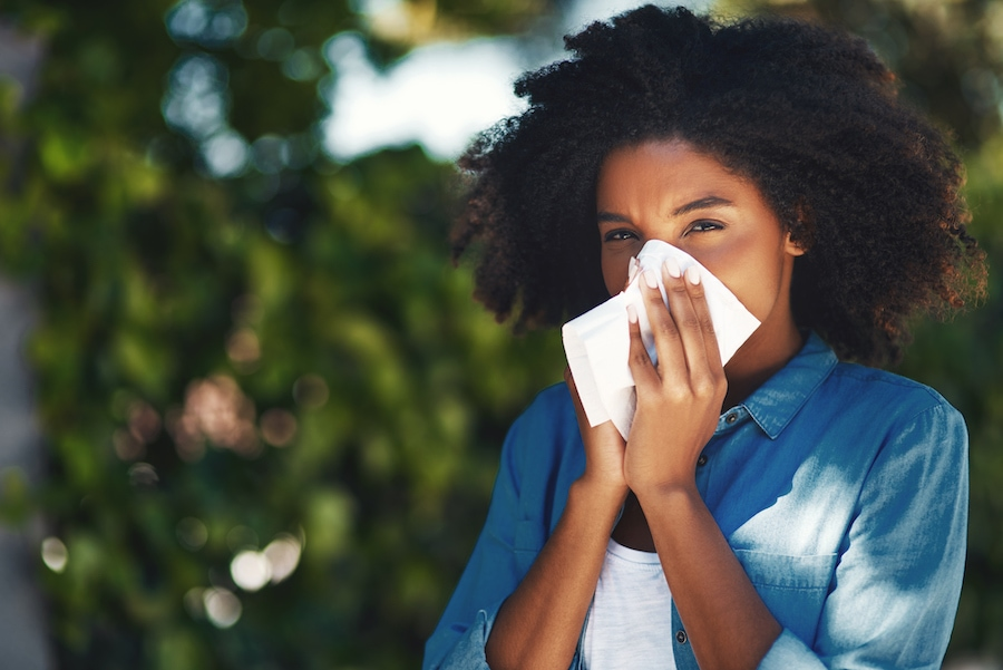 Woman blowing nose due to allergy symptoms