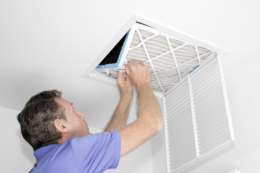 Technician replacing air filter in home to help eliminate mold growth.