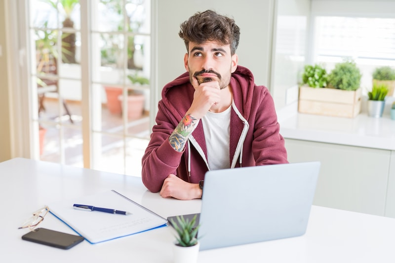 Young student man using computer laptop and notebook serious face thinking about question, very confused idea
