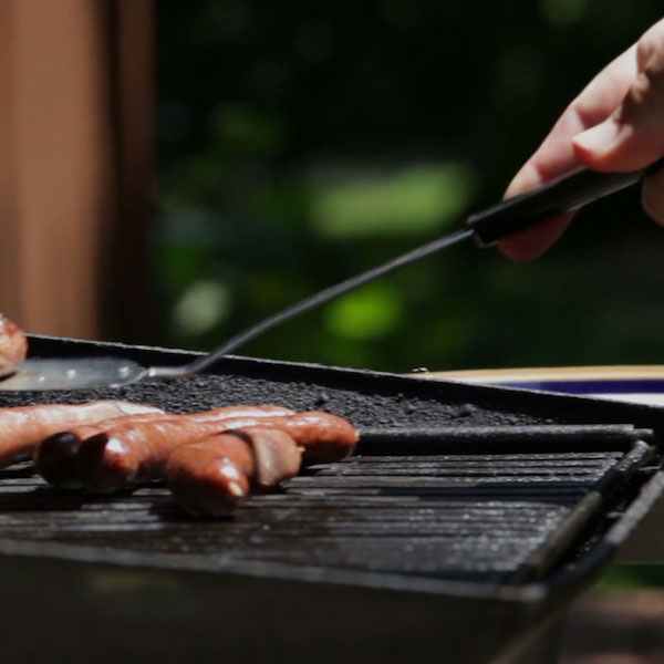 cooking hot dogs on the grill in summer.