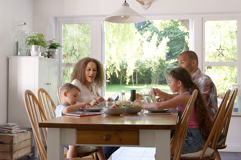 family of four sitting around the kitchen table eating lunch.