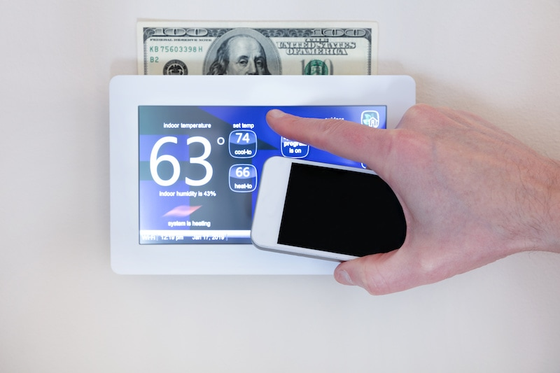 Male hand holding smart phone to operate heating or cooling of thermostat for home energy savings