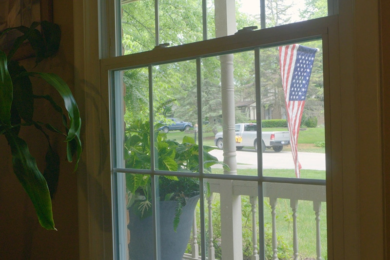 Window view of outside where there is an American Flag hanging.
