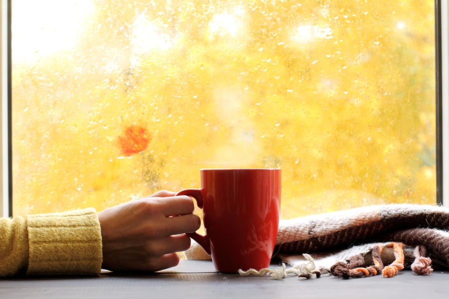 red mug of hot drink, when behind a window is rain in autumn in Grayslake, IL